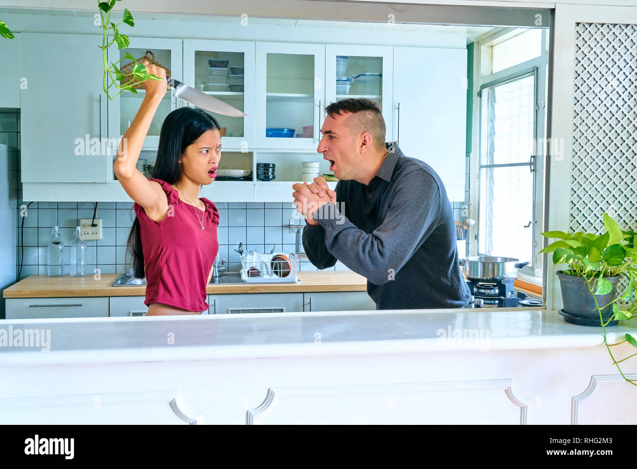 Lovely couple posing - man begging to his woman not to kill him - Stock Image