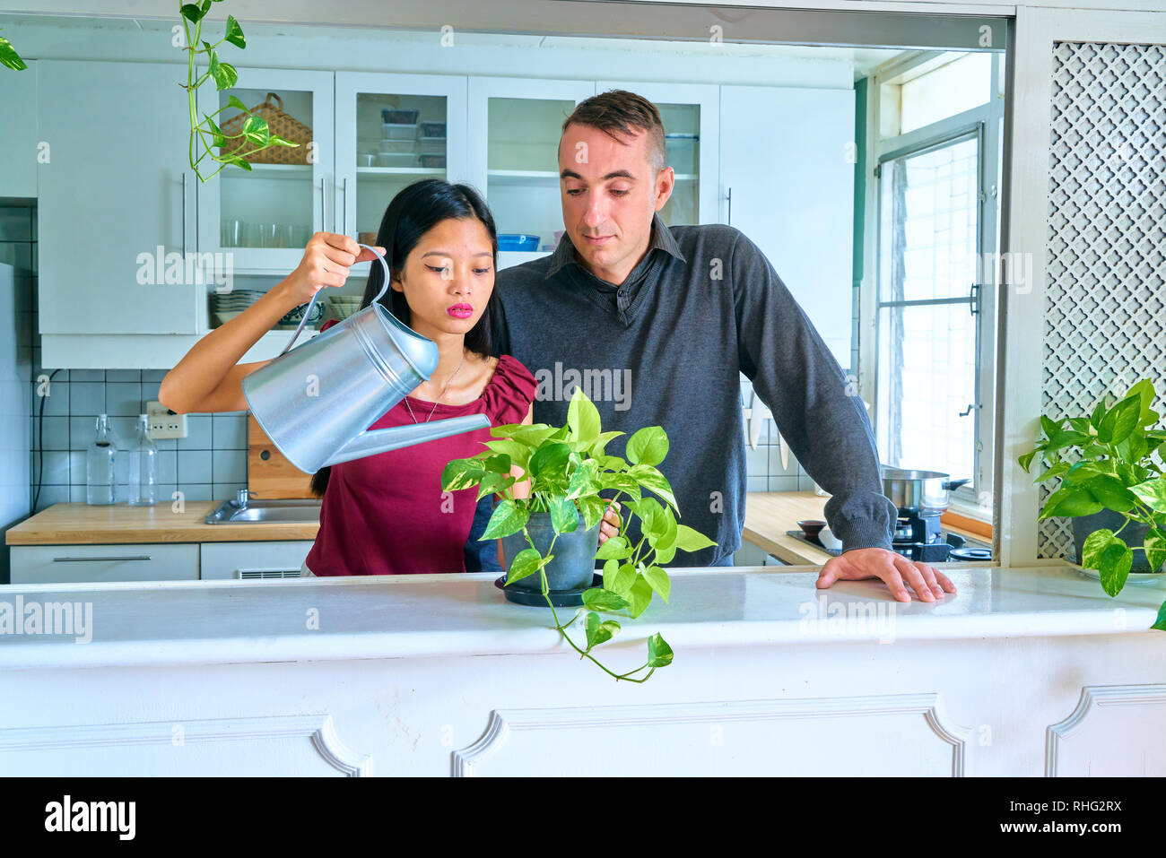 Lovely couple posing - watering the plants - Stock Image
