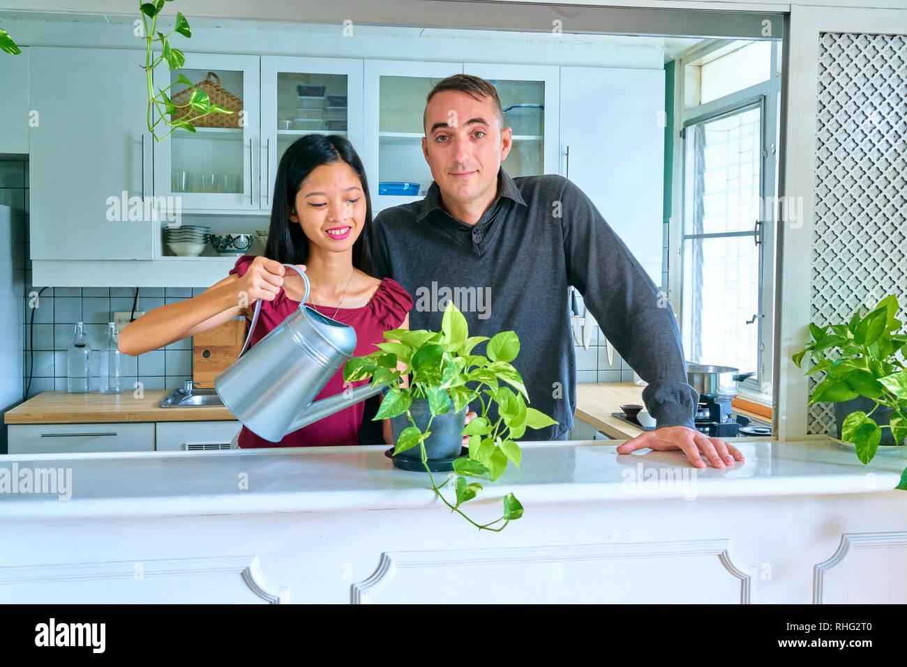 Lovely couple posing - enjoying to watering plants - Stock Image