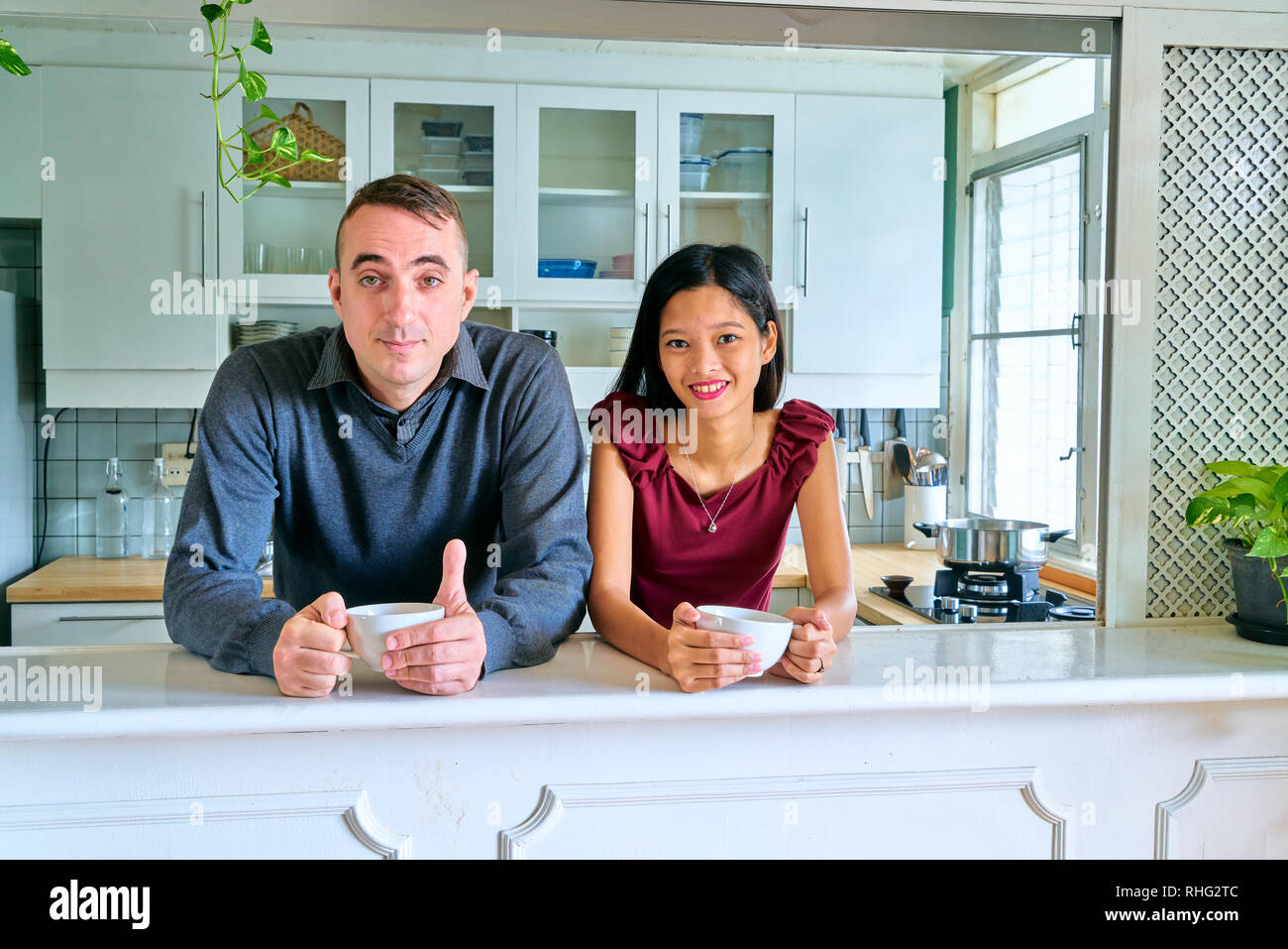 Lovely couple posing - holding of cup and looking at camera - Stock Image