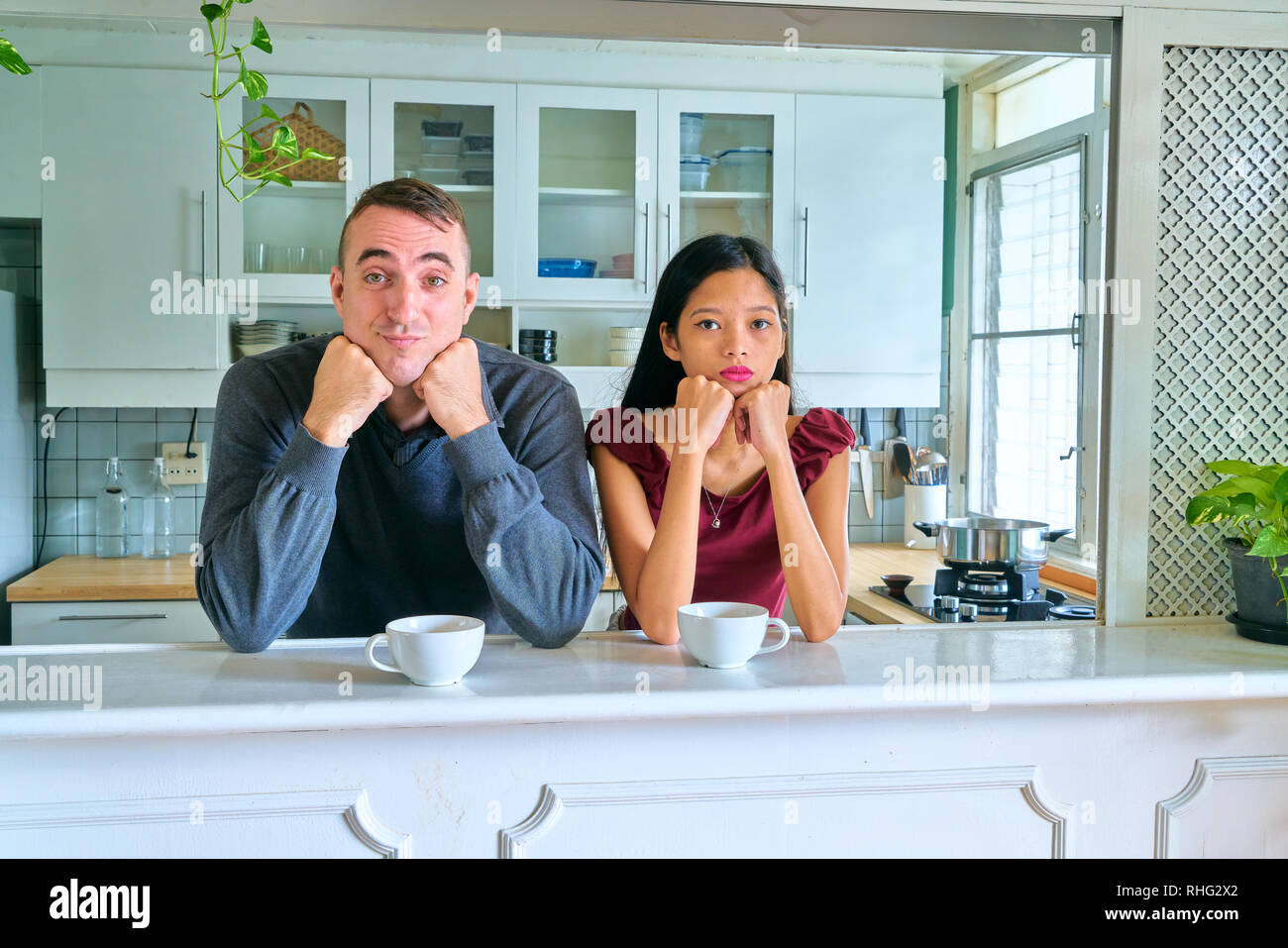 Lovely couple posing - hand on chin and looking at camera - Stock Image