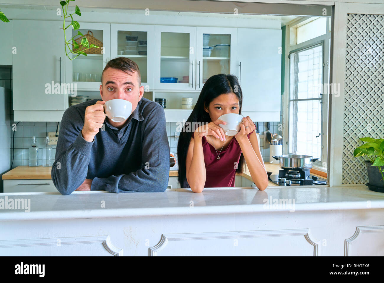 Lovely couple posing - drinking coffee and looking at camera - Stock Image