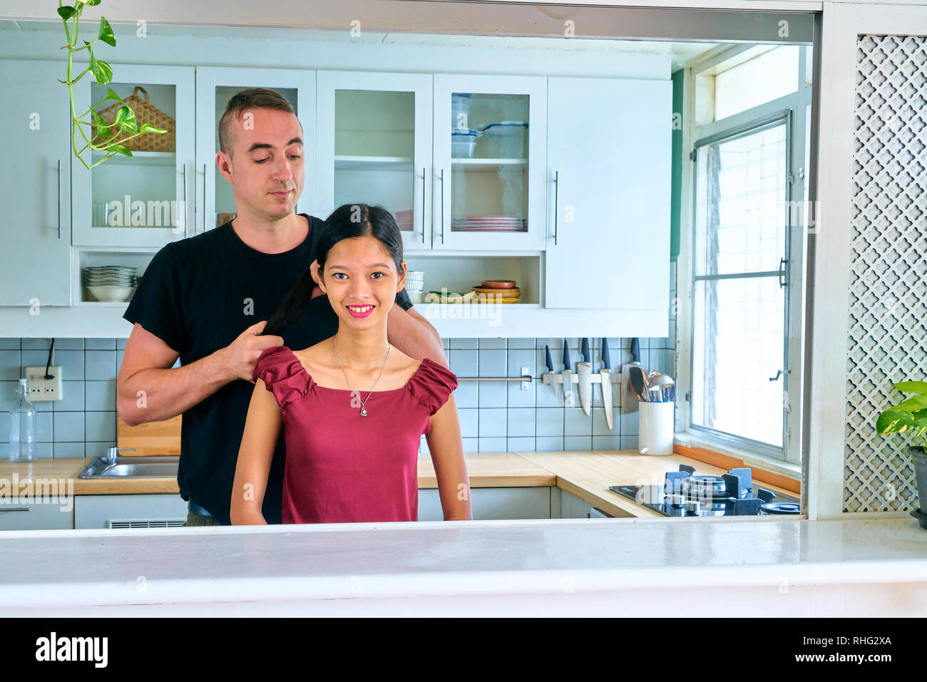 Lovely couple posing - man combing her hair and young woman looking at camera - Stock Image