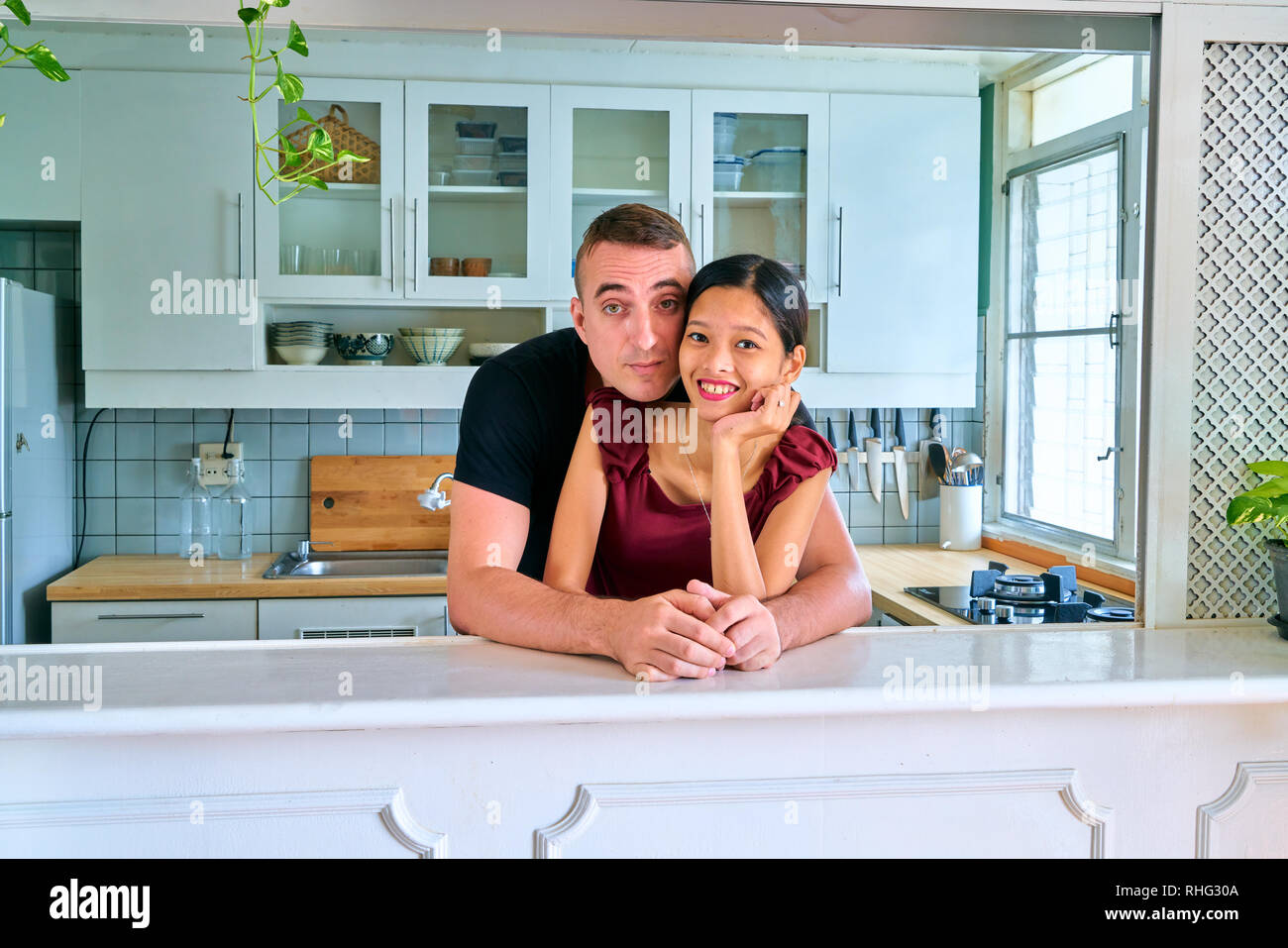 Lovely couple posing - hand on chin with smiling face and hugging - Stock Image