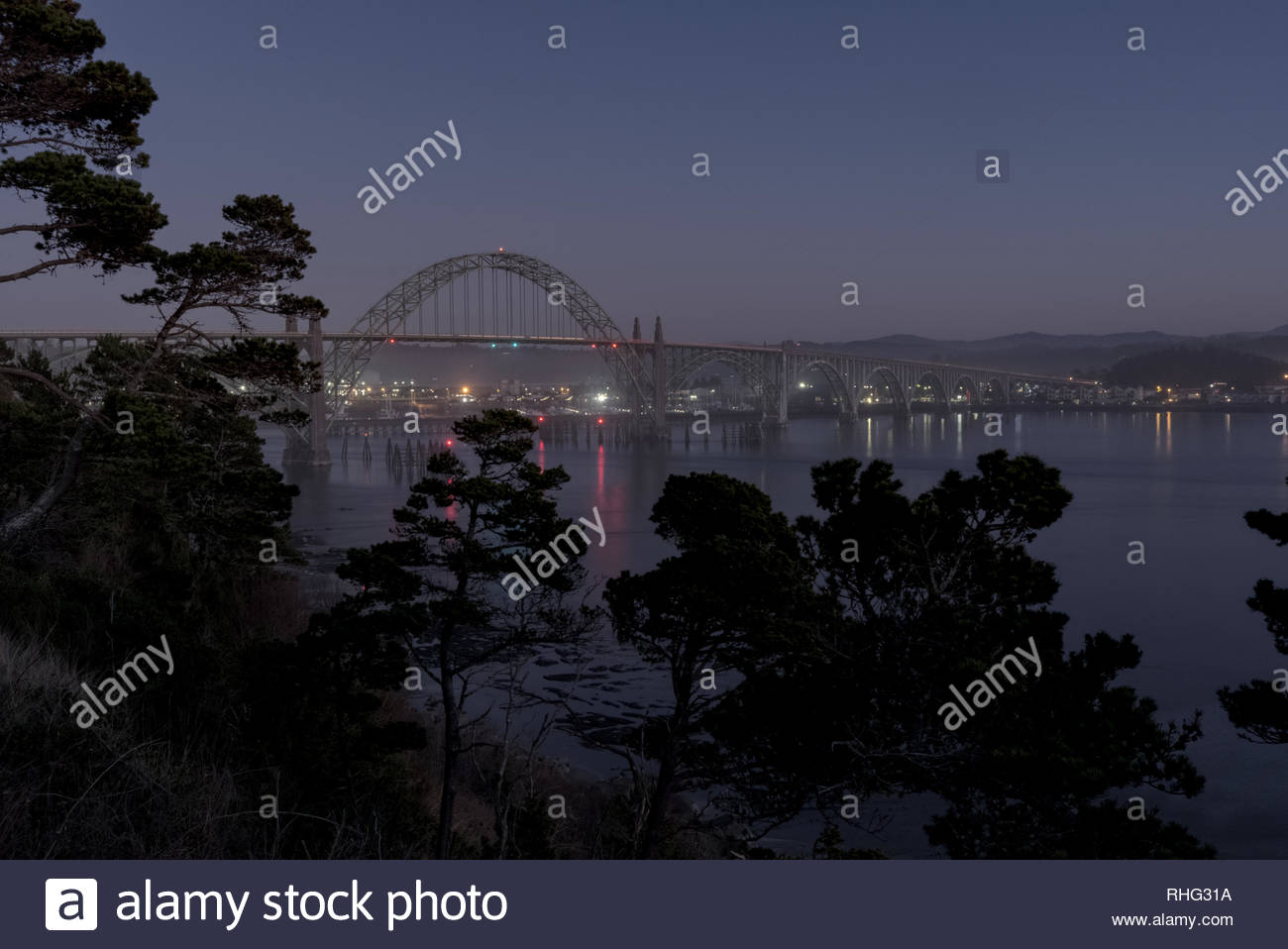 Yaquina Bay Bridge at dusk, Newport, Oregon. Silhouetted trees in foreground frame bridge. - Stock Image