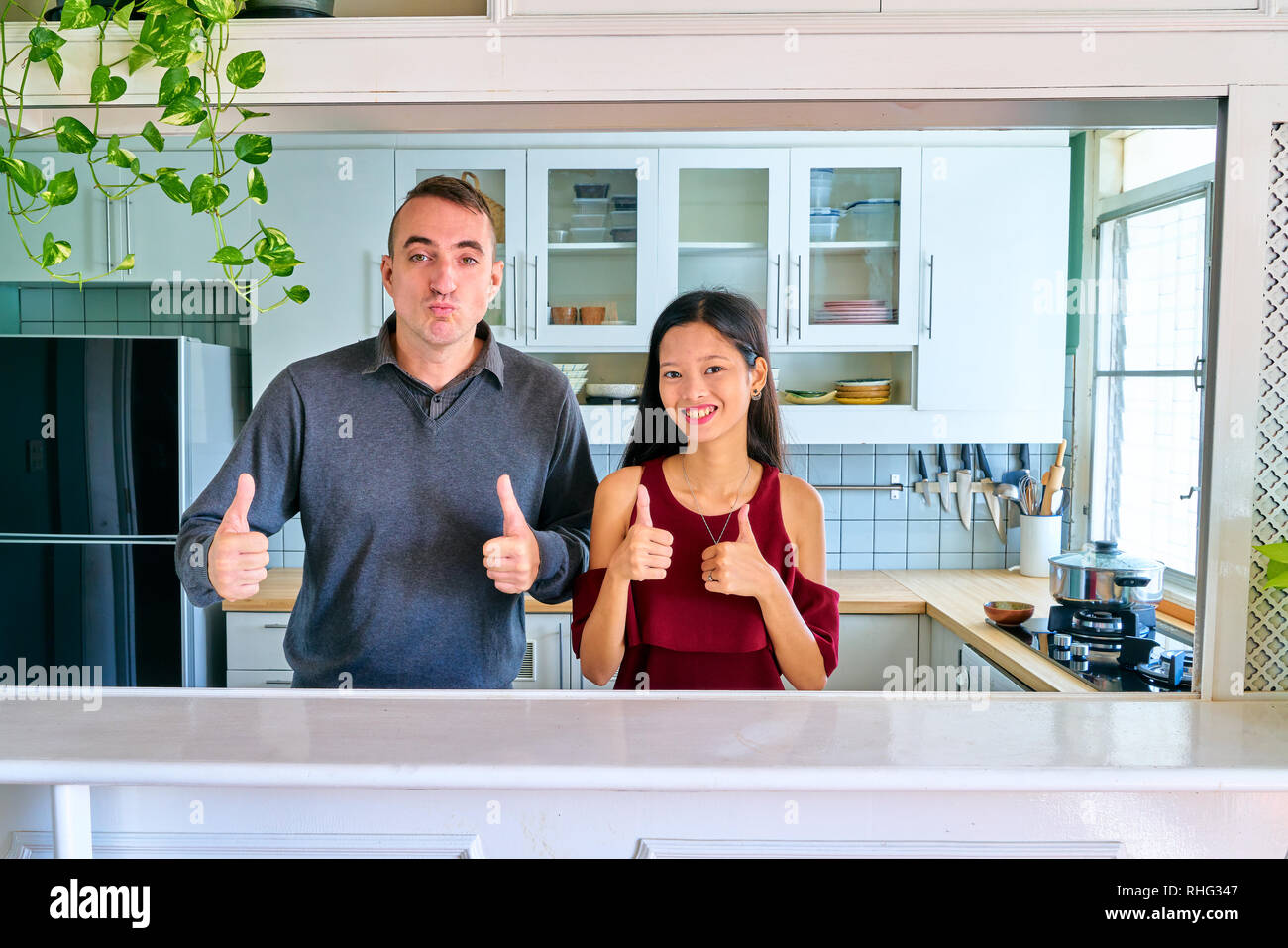 Lovely couple posing - thumbs up gesture and smiling young woman - Stock Image