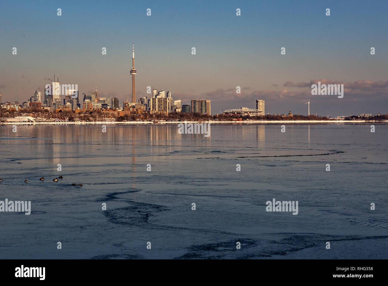 Panoramic Canadian winter landscape near Toronto, beautiful frozen Ontario lake at sunset. Scenery with winter trees, water and blue sky. - Stock Image