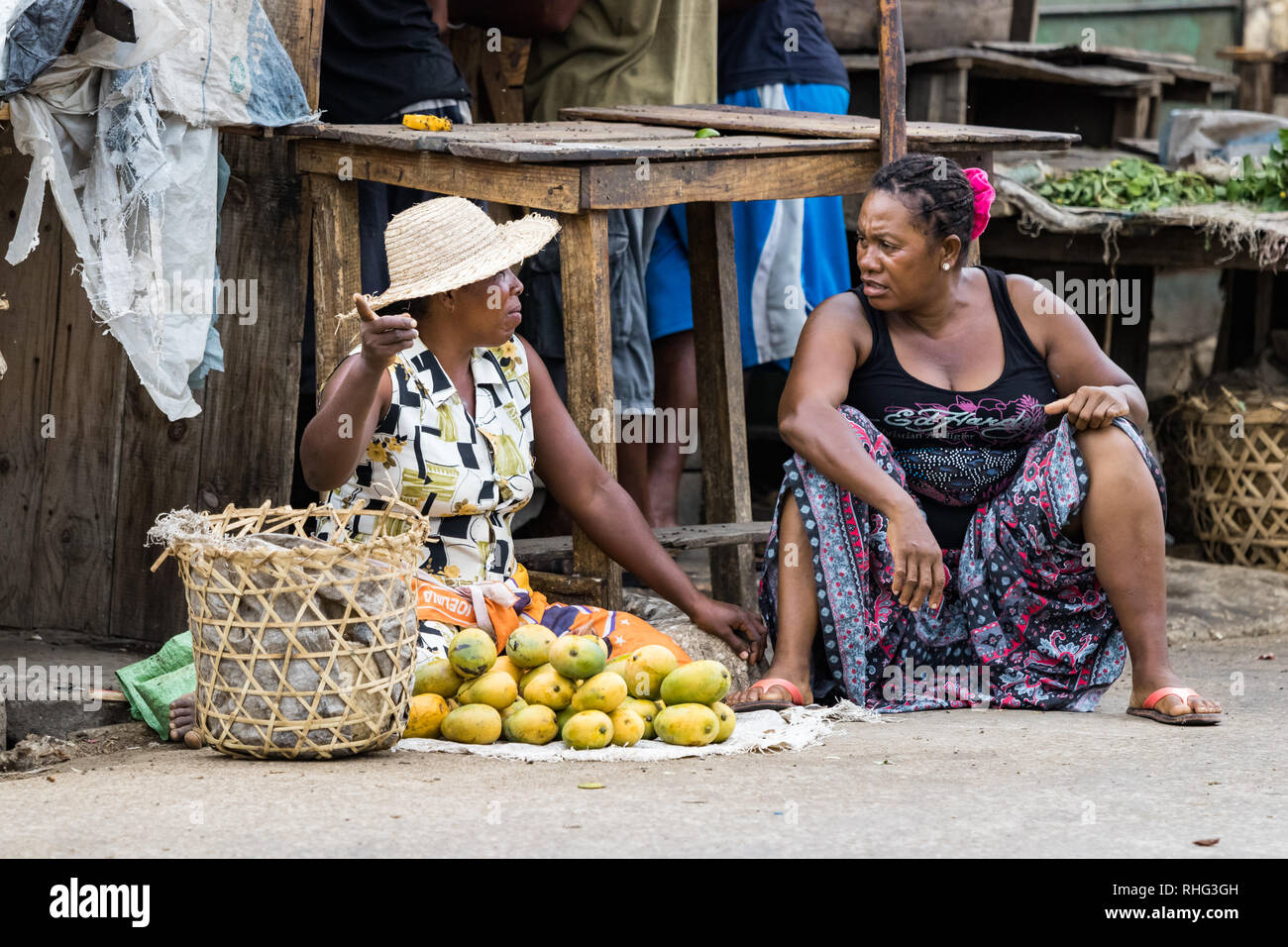 Toliara, Madagascar - January 10th, 2019: Two Malagasy women street vendors discussing sitting on the pavement at the local food market in Toliara, Ma - Stock Image