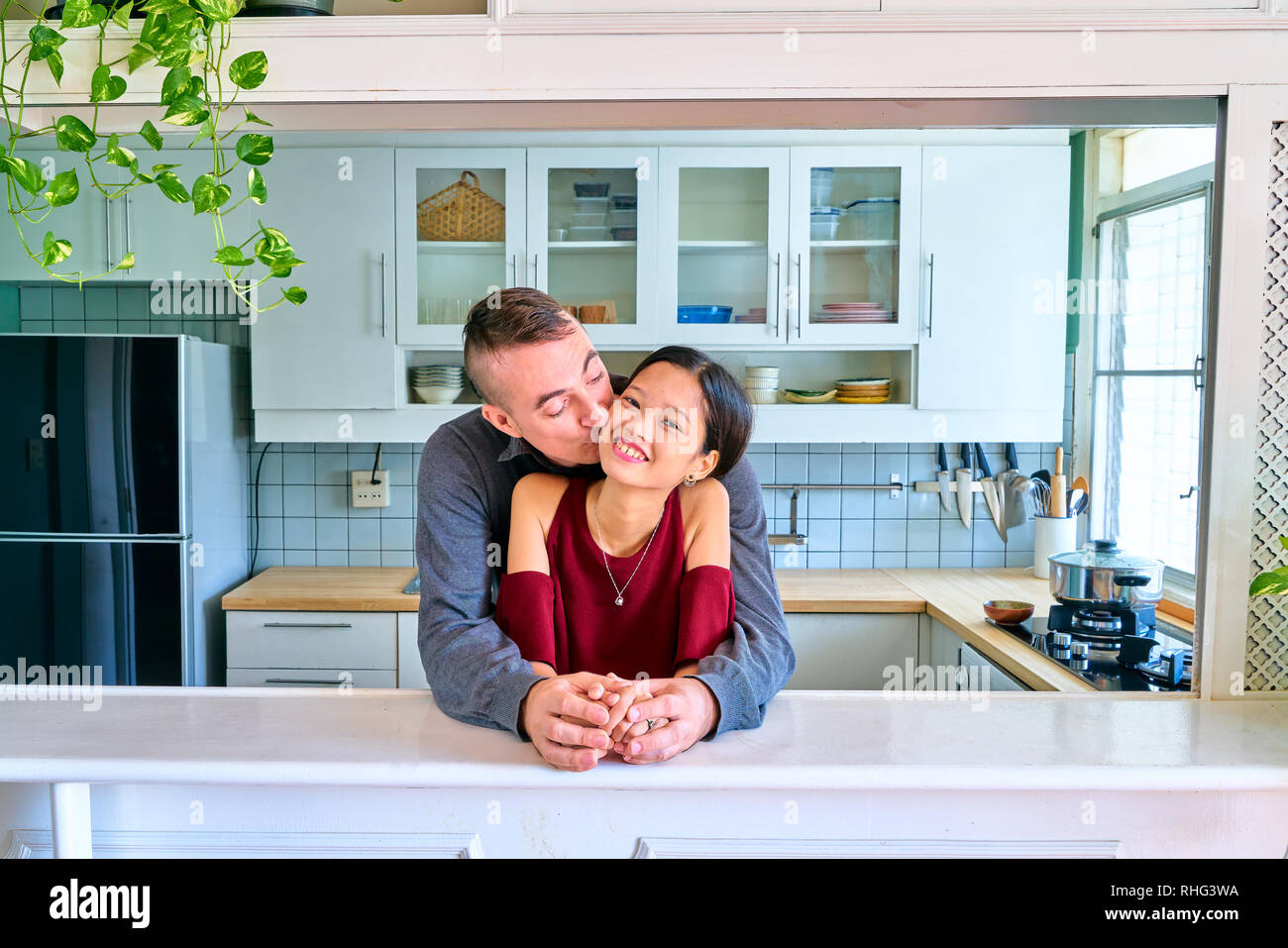 Lovely couple posing - holding hands and kissing cheek - Stock Image