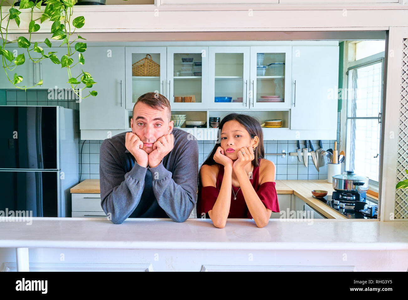 Lovely couple posing - bored, tired and looking at camera - Stock Image