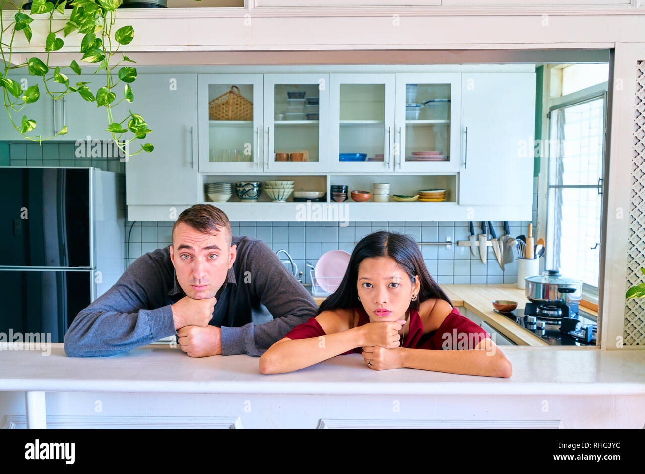 Lovely couple posing - fist on chin and looking at camera - Stock Image