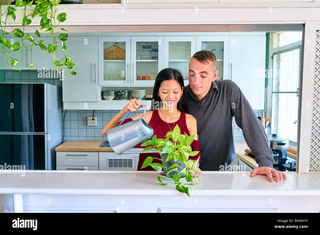 Lovely couple posing - watering plants and taking care the plants - Stock Image