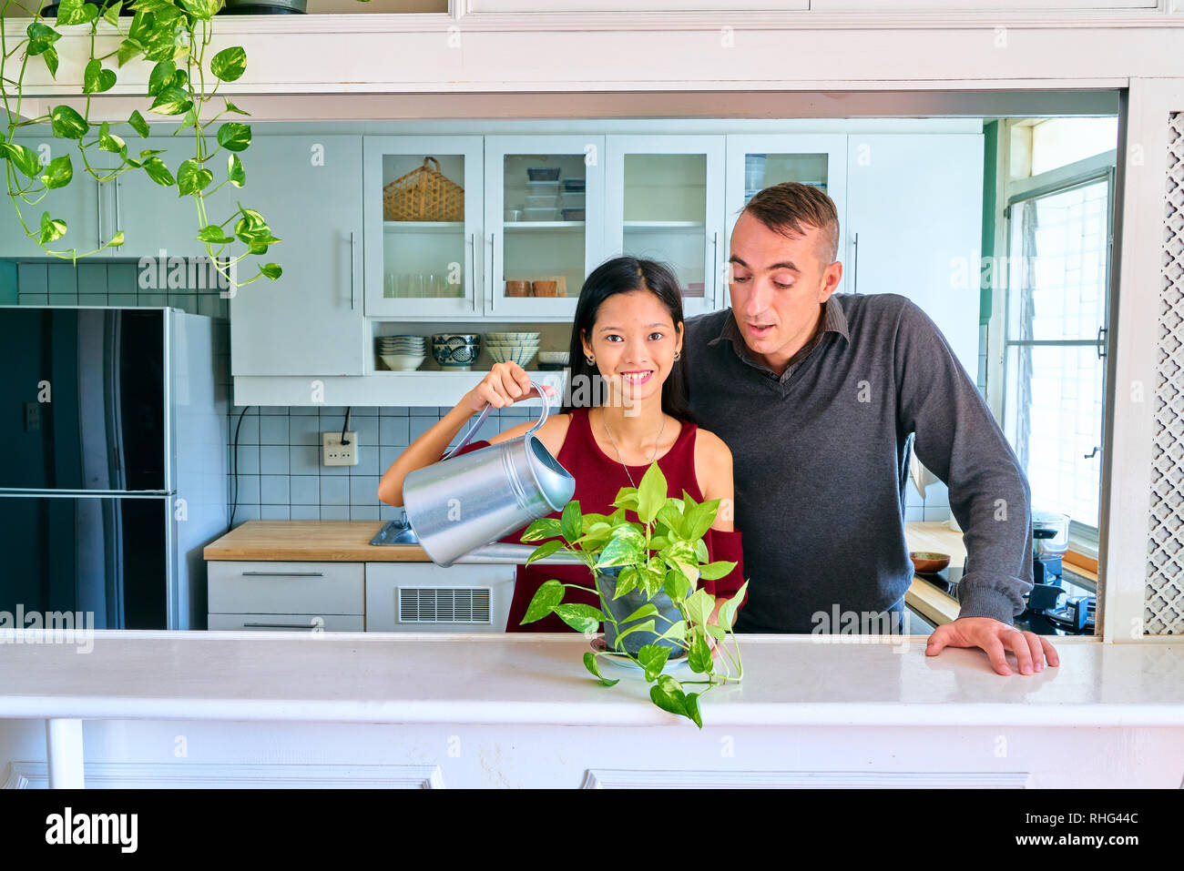 Lovely couple posing - watering plants and looking at camera - Stock Image
