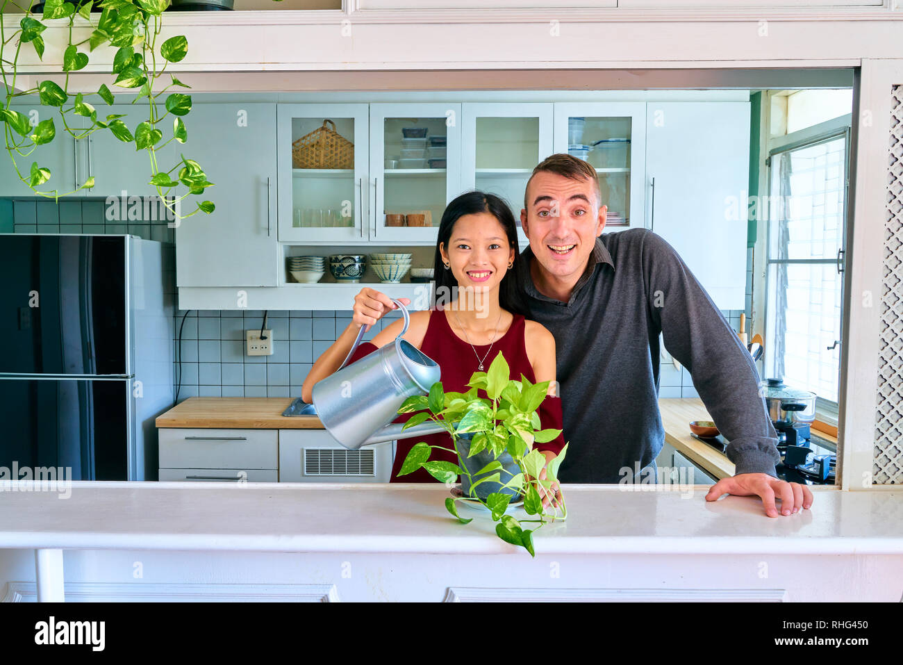 Lovely couple posing - watering plants, smiling and looking at camera - Stock Image