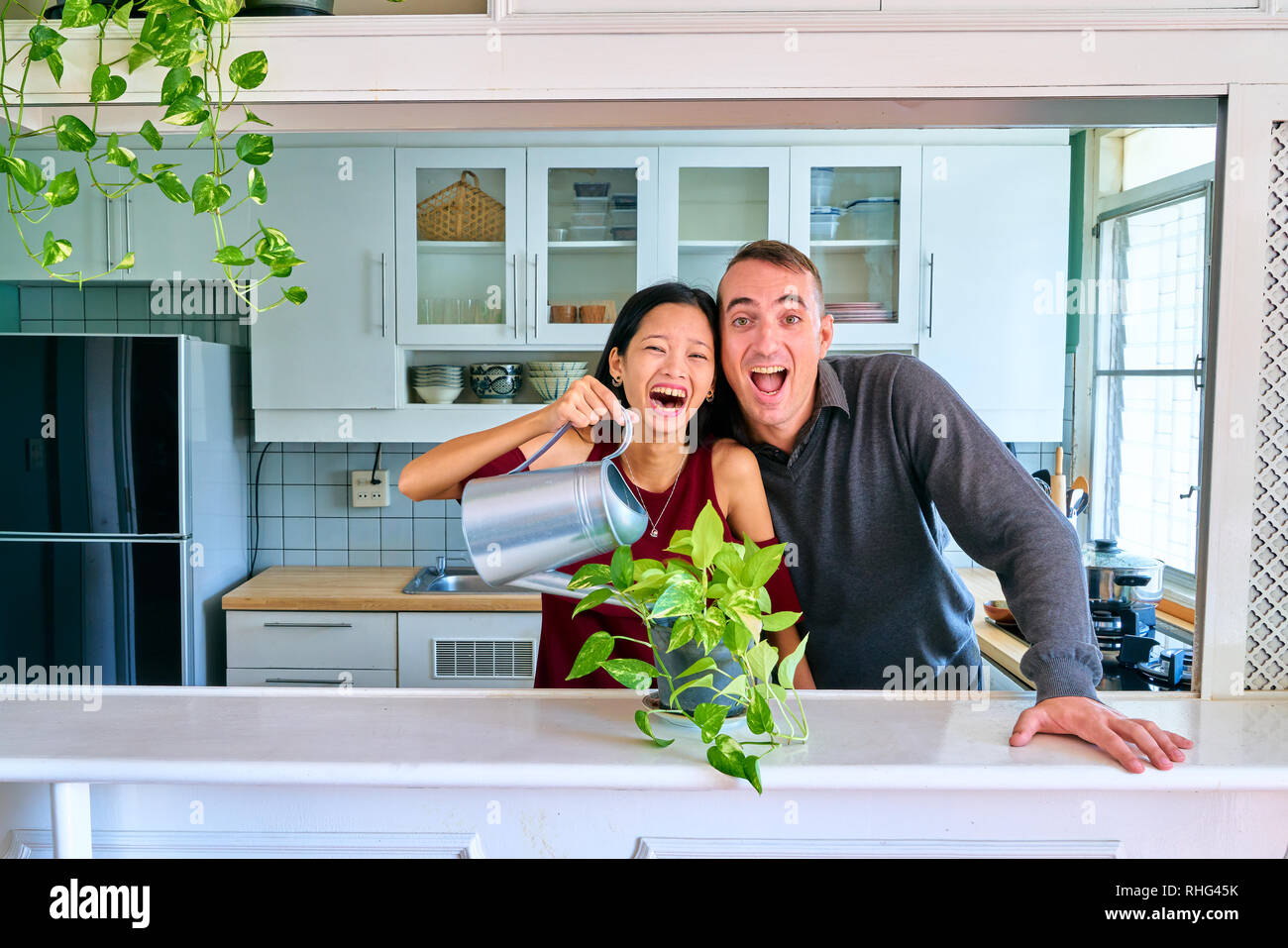 Lovely couple posing - watering plants and laughing each other - Stock Image