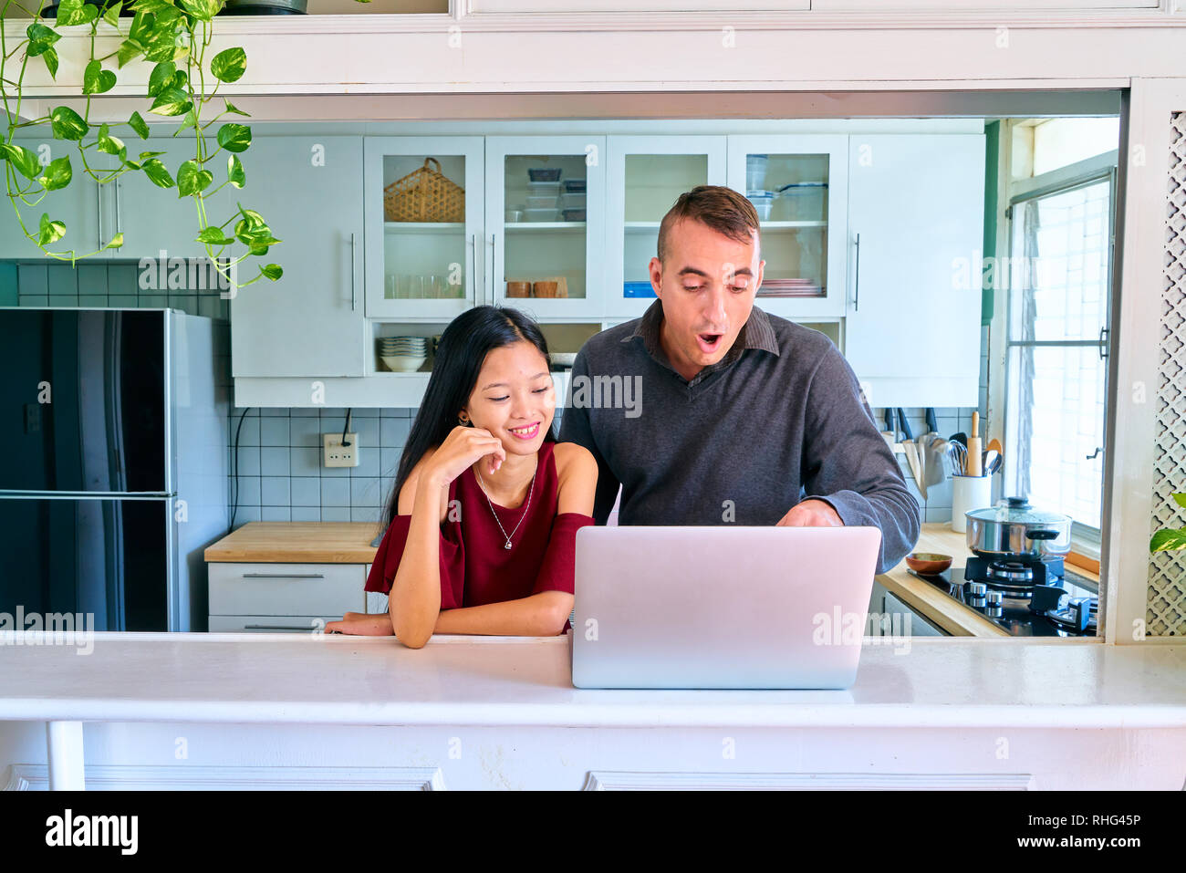 Lovely couple posing - watching movies on laptop and pointing and shocked - Stock Image
