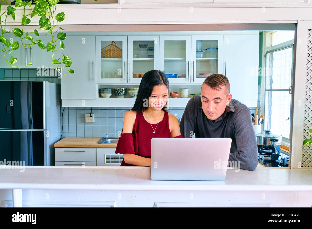 Lovely couple posing - searching something on laptop - Stock Image