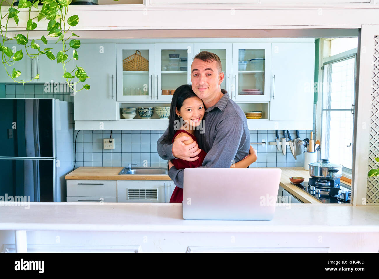 Lovely couple posing - hugging, smiling and looking at camera - Stock Image