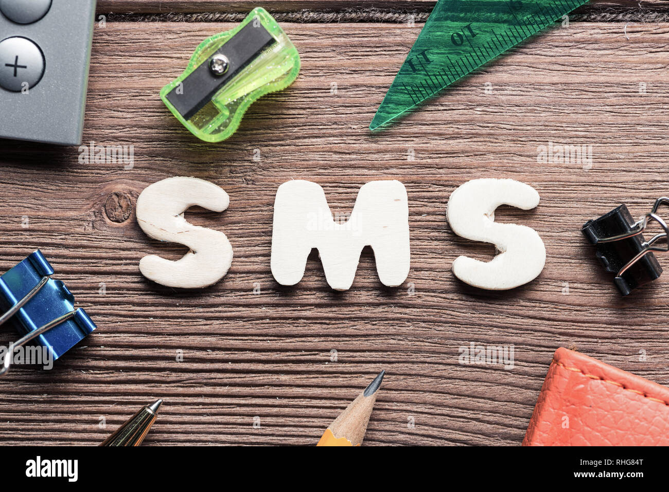 SMS word on wooden table and office stationary around - Stock Image