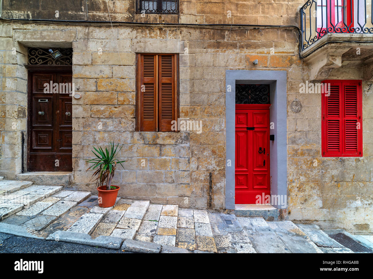 Front view of stone house with typical colorful wooden doors in Valletta, Malta. - Stock Image