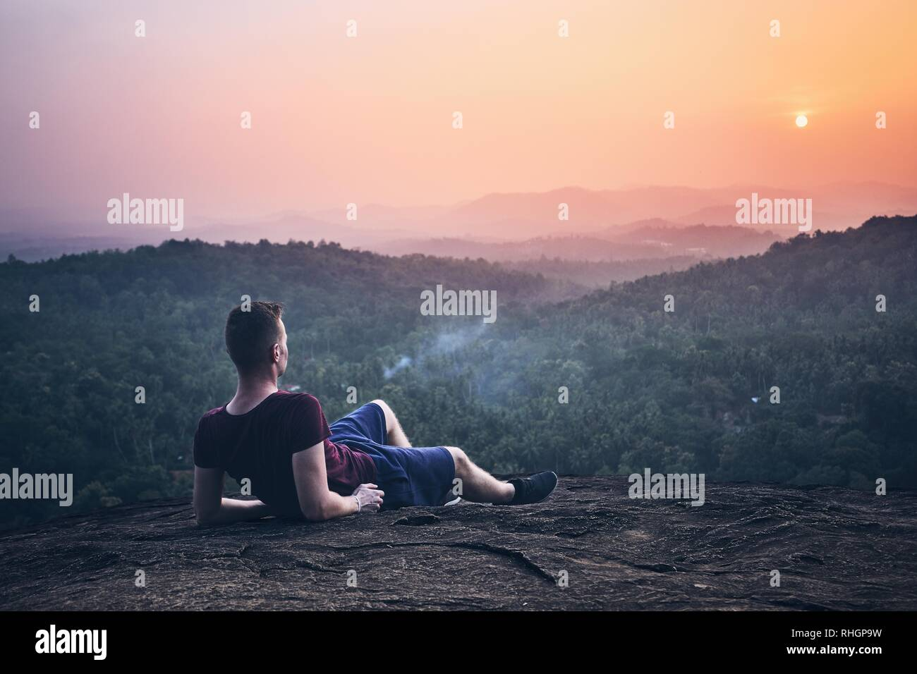Young man contemplation on top of rock. Landscape at sunset in Sri Lanka. - Stock Image