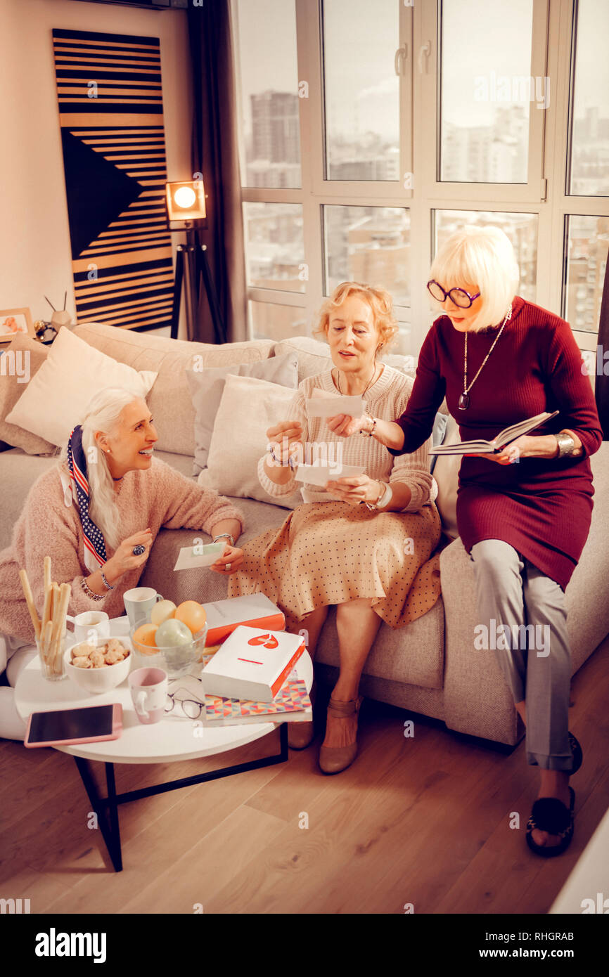 Pleasant elderly women looking at old photos - Stock Image