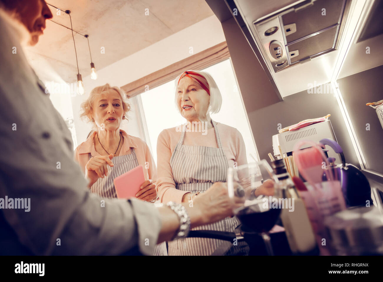 Positive nice aged women helping each other Stock Photo