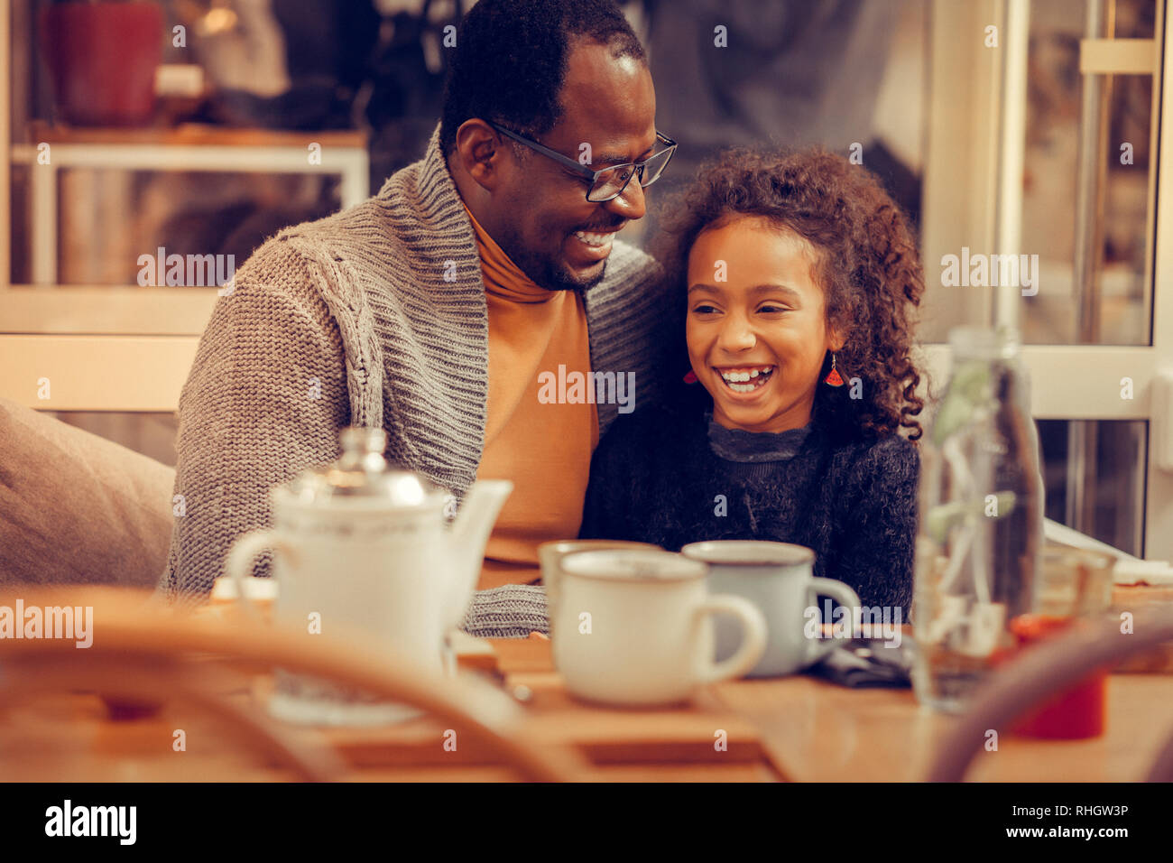 Cheerful cute curly daughter laughing while speaking with father - Stock Image