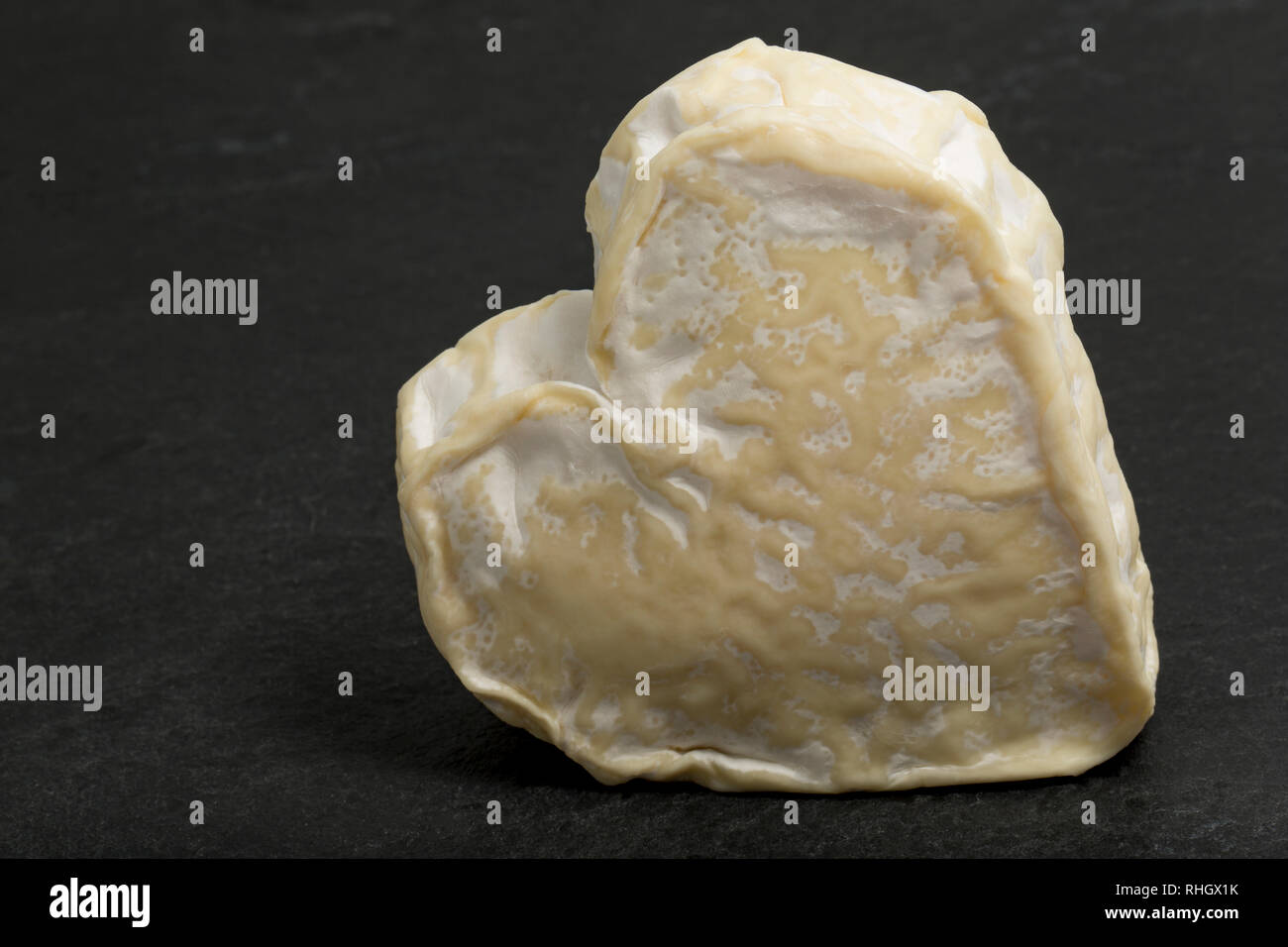 A heart-shaped Neufchatel cheese, from Normandy, France made from cows milk, photographed on a dark, slate background. England UK GB - Stock Image