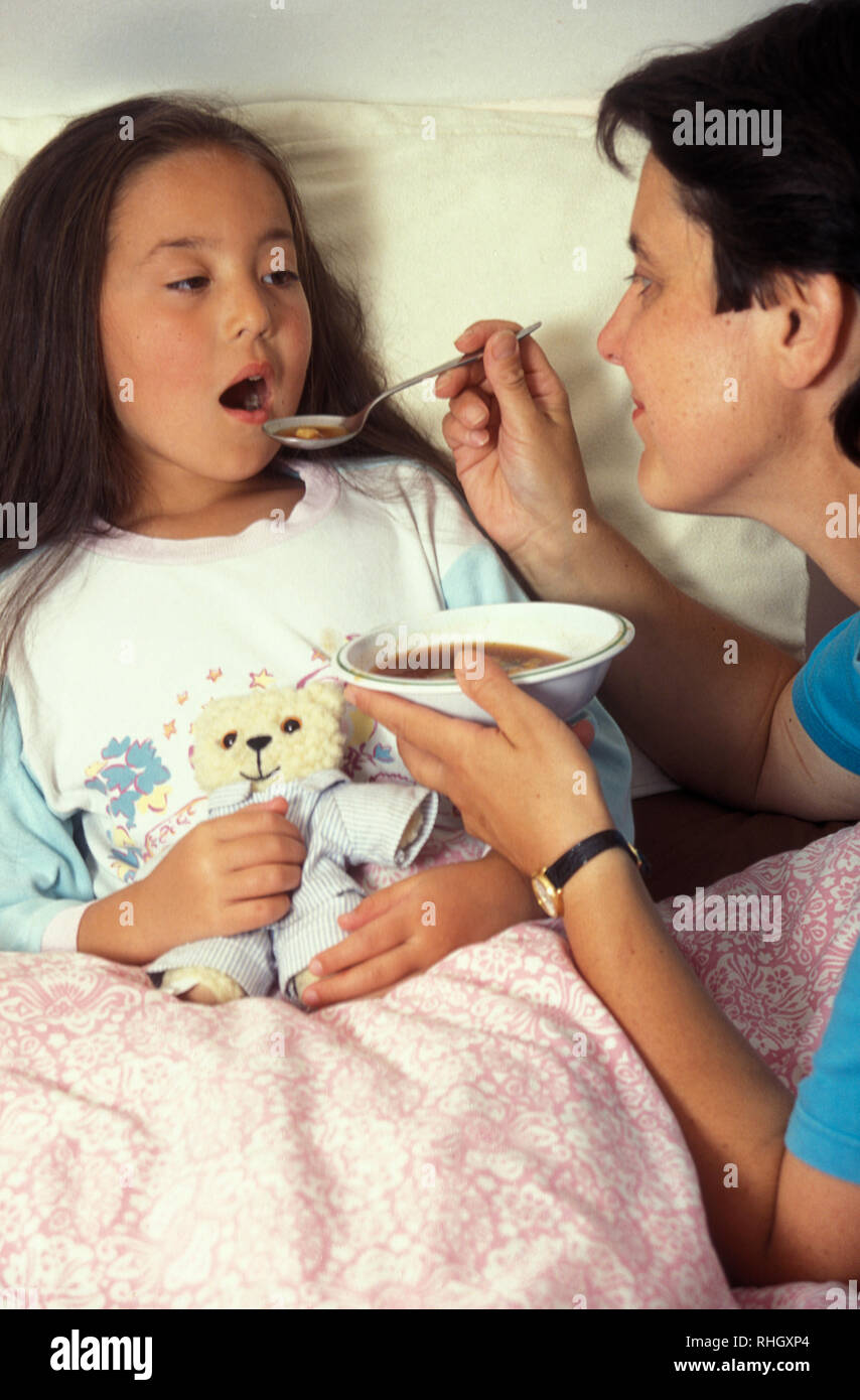 mother serving soup to little girl sick in bed - Stock Image