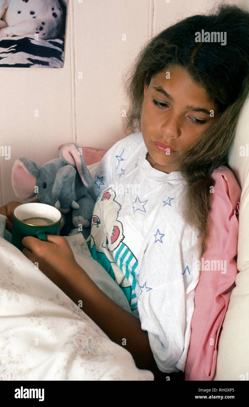 girl sick in bed with hot drink - Stock Image