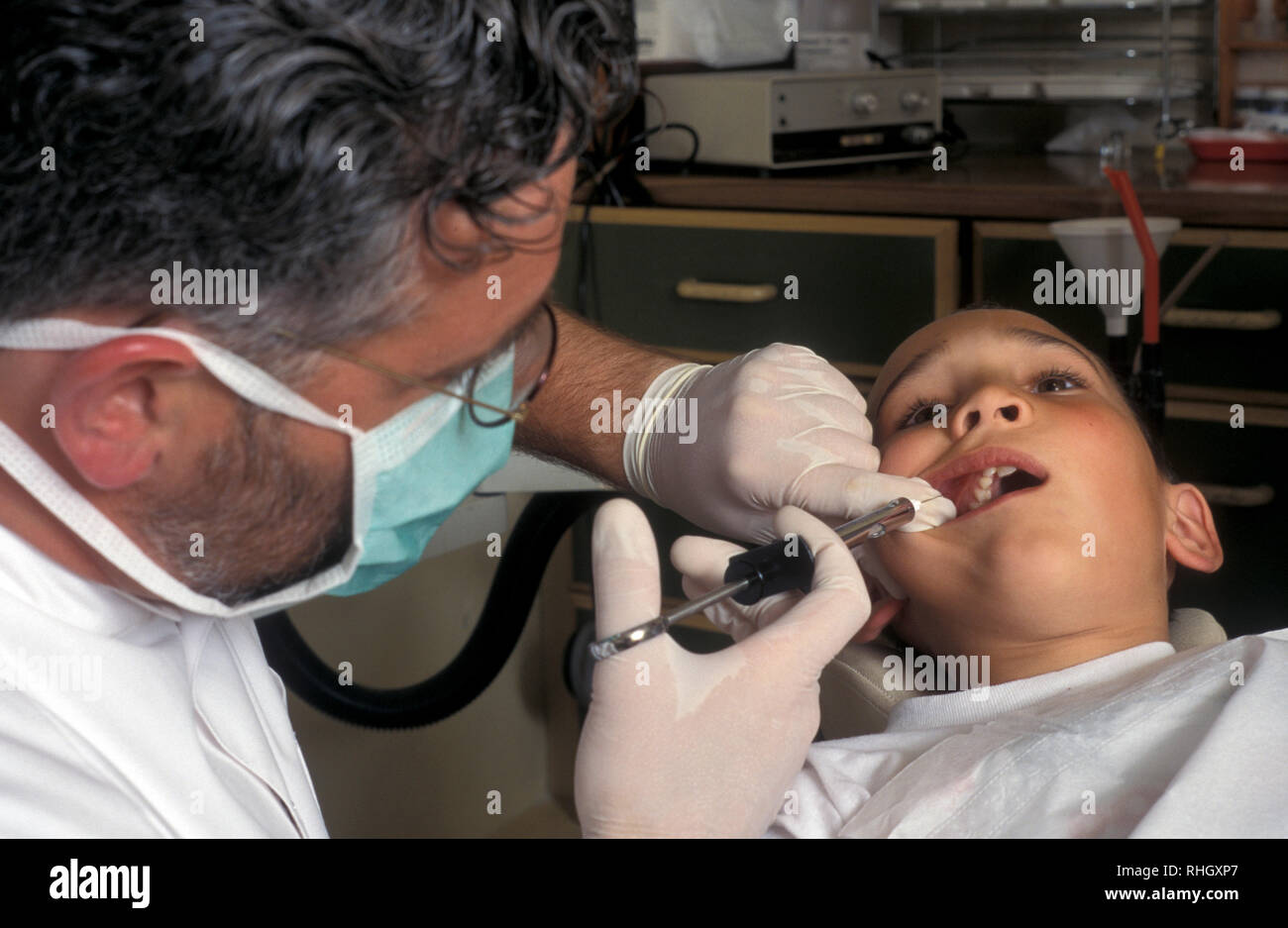 dentist giving little boy novocaine injection Stock Photo