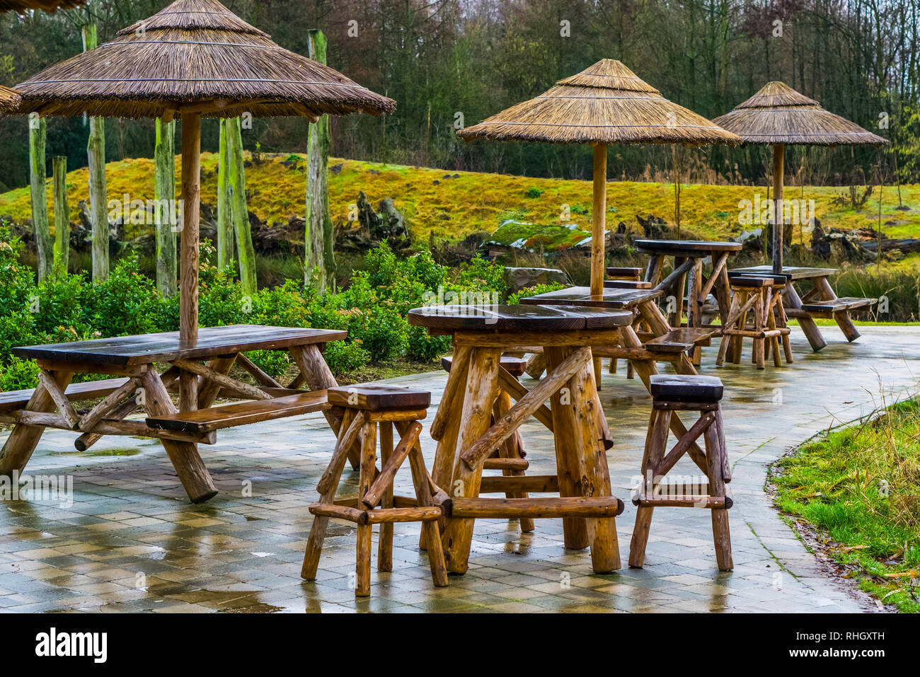 exotic looking bar that is empty on a rainy day, terrace and garden furniture, bad day in the catering industry - Stock Image