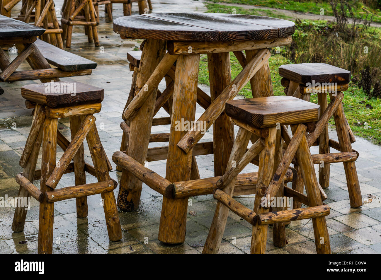 empty wooden table with bar crutches, garden or terrace furniture, rainy day in the catering industry - Stock Image
