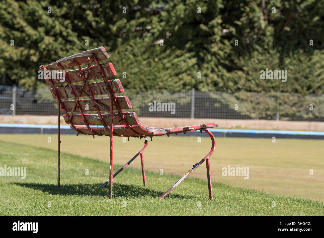 An old park bench sits beside a bowling green at Club Milthorpe, AKA The Milthorpe Lawn Bowls Club in central western New South Wales, Australia - Stock Image