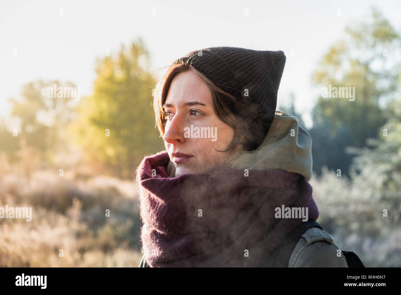 Backlit portrait of beautiful breath misting woman. Female person walking outdoors on chilly sunny morning in autumn Stock Photo