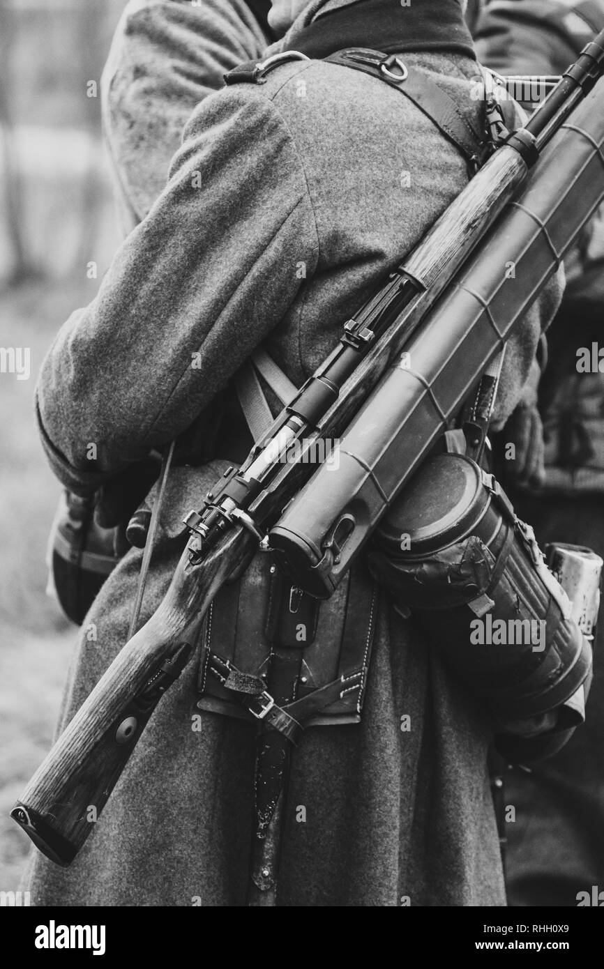 Wehrmacht soldiers in their overcoats with a rifle on their backs, uniforms of German soldiers in World War II. Black and White Photo - Stock Image