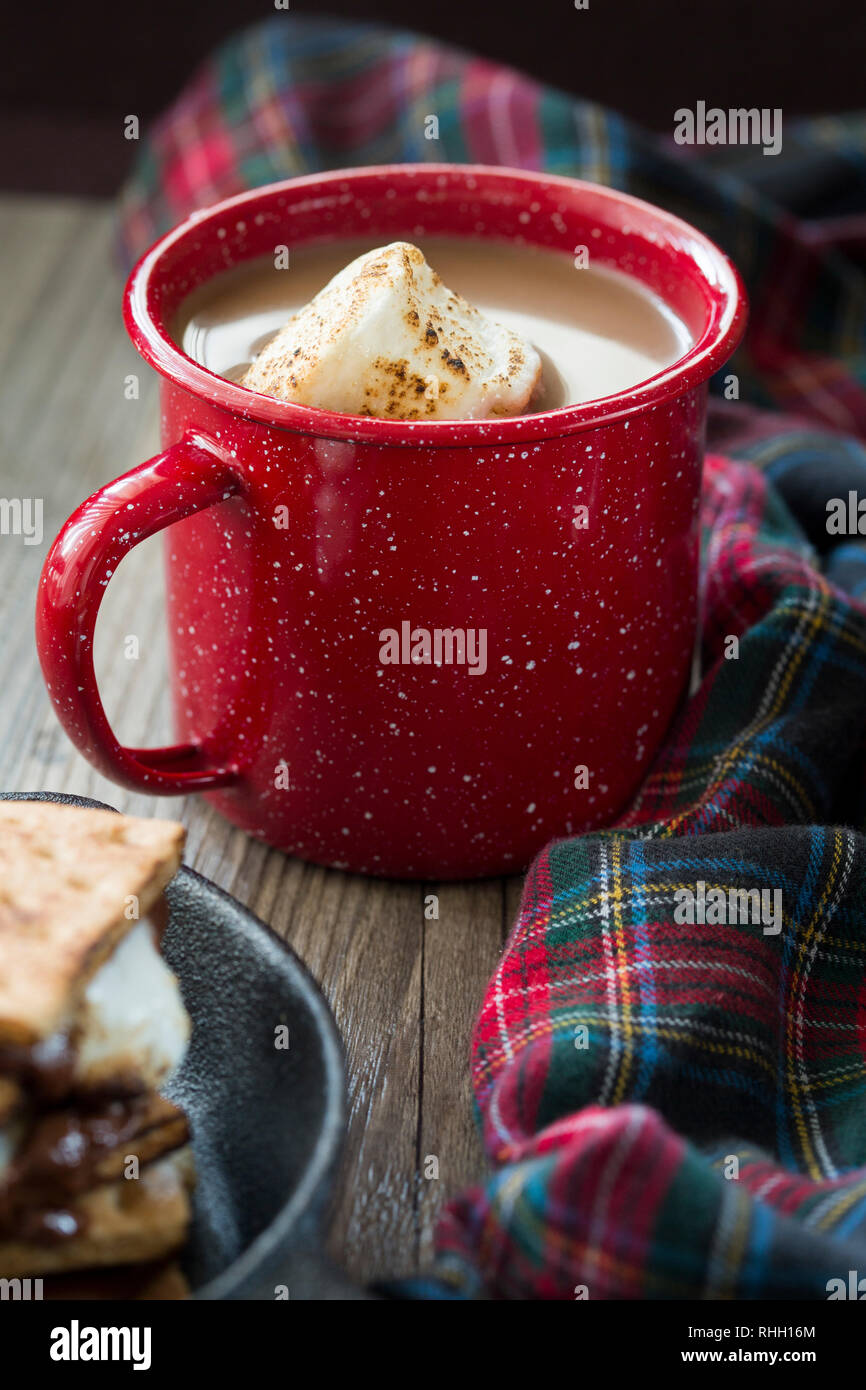 mug of hot chocolate with toasted marshmallow in red speckled enamelware mug with plaid blanket and smores - Stock Image