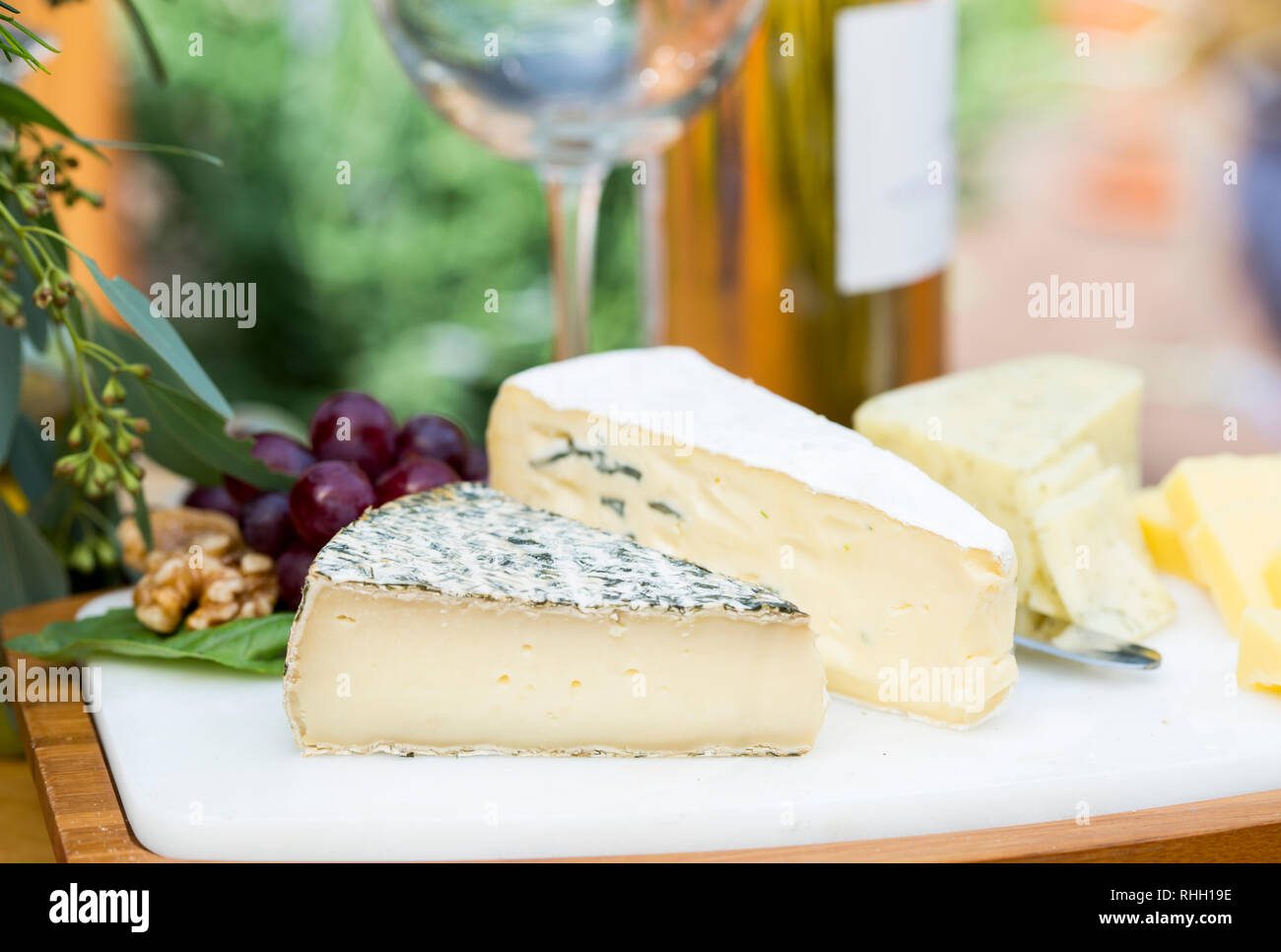 Three large wedges of cheese on marble cheese board- outdoor al fresco entertaining. - Stock Image