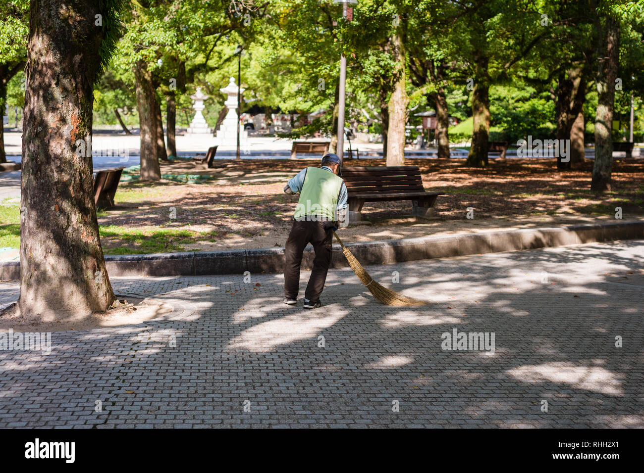 and old man sweeping in the park. Staying active in retirement is one of the secrets of Japan's long life expectancy - Stock Image