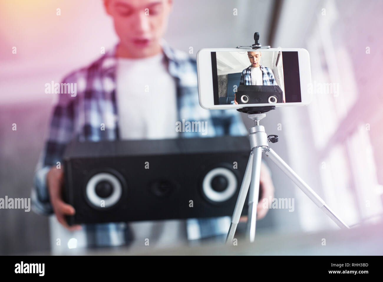 Handsome student filming video about birthday presents using photo stand - Stock Image