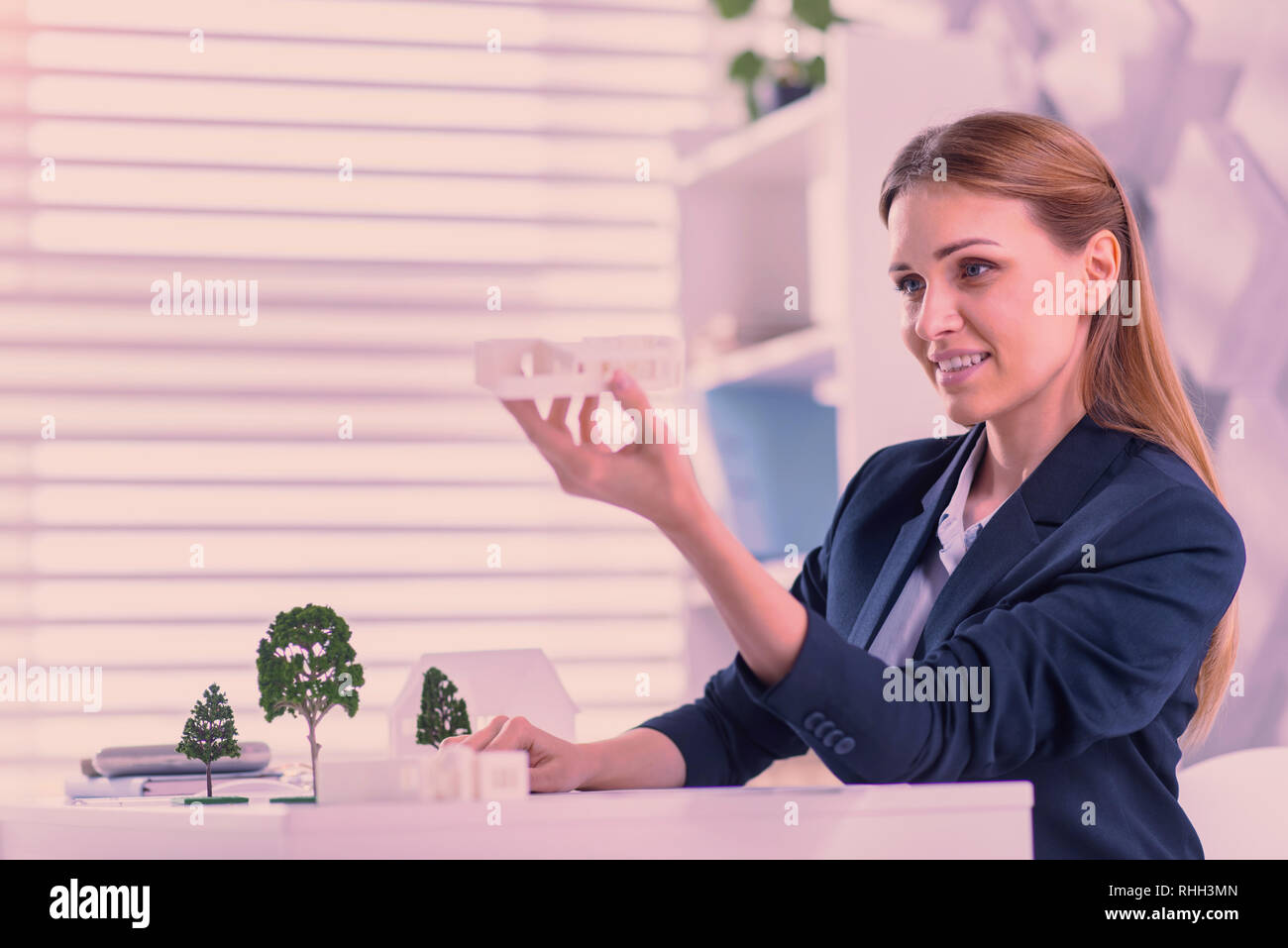 Attractive female architect elevating models at office - Stock Image