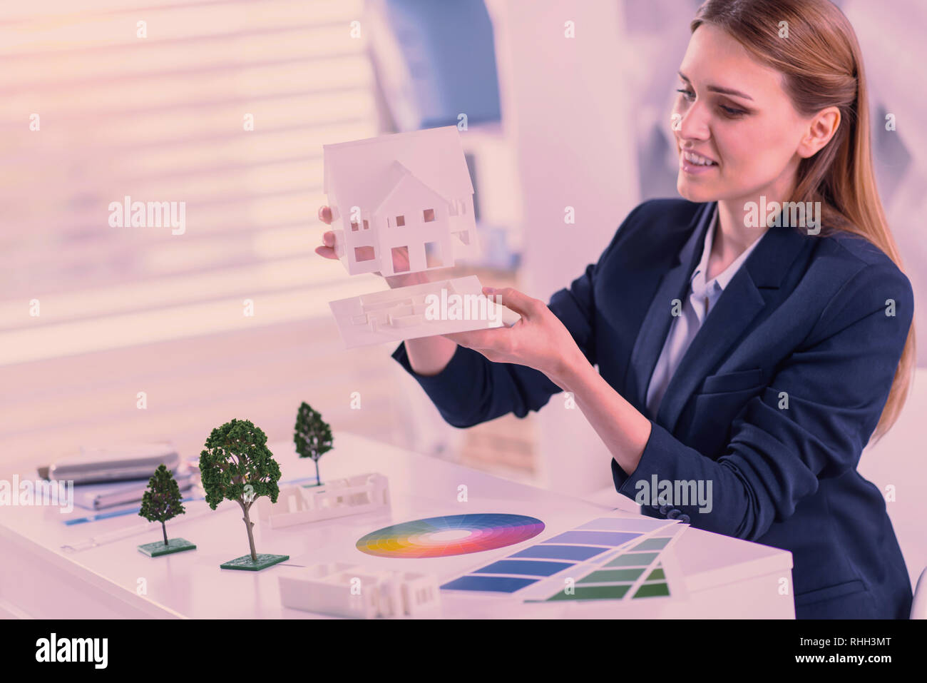 Beautiful female architect combining models at office - Stock Image
