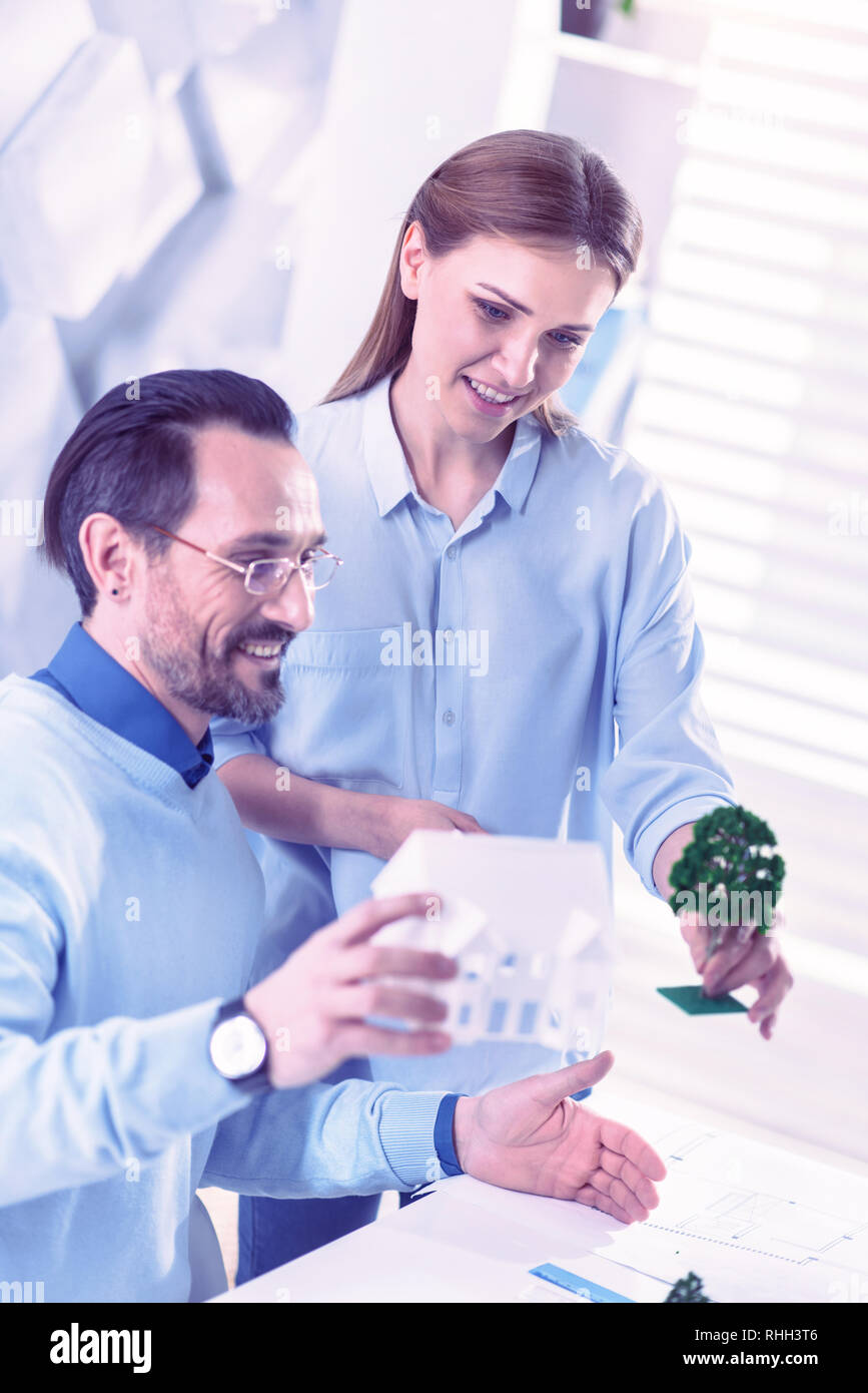 Friendly engineers smiling and looking interested while working with little models - Stock Image