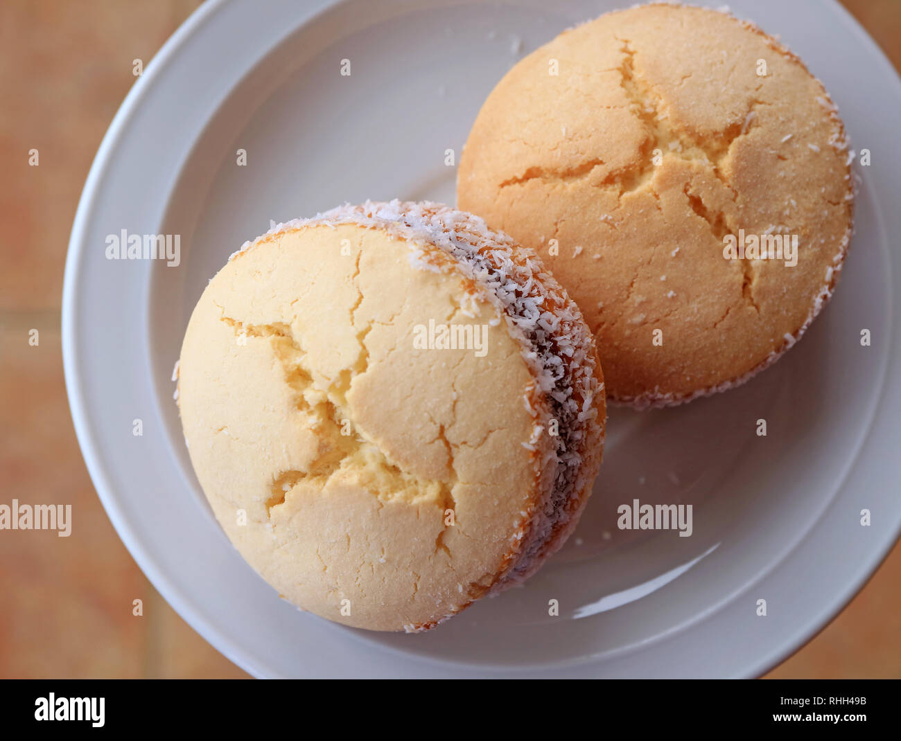 Top view of two Alfajores, traditional Latin American sweets served on a white plate Stock Photo