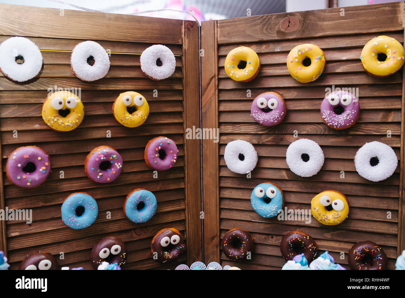 Yummy donuts hanging over wooden folding screen. White yellow, chocalate and white coating with faces. Glaze. Stock Photo