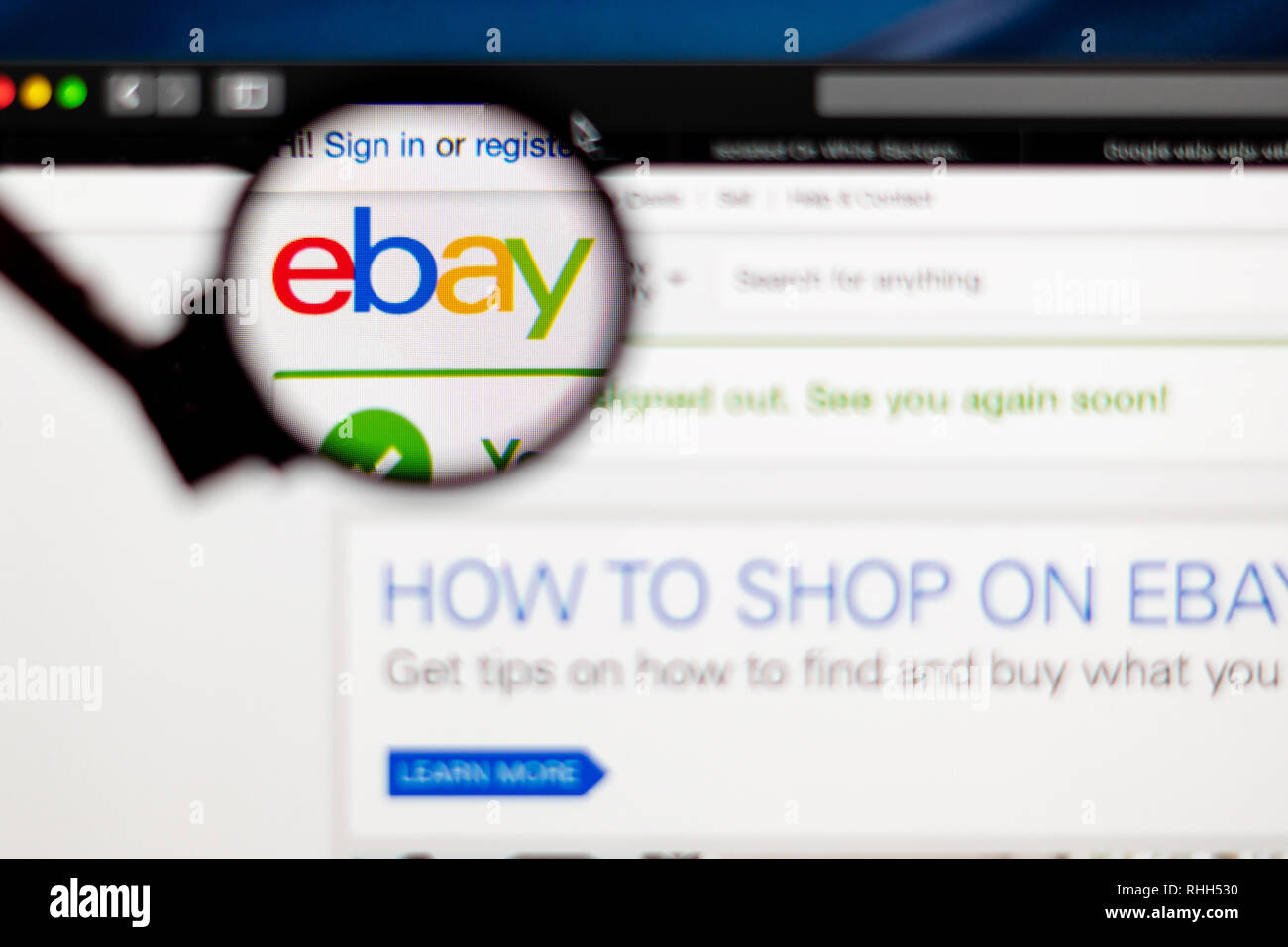 eBay website homepage. eBay company logo visible  through a magnifying glass. - Stock Image