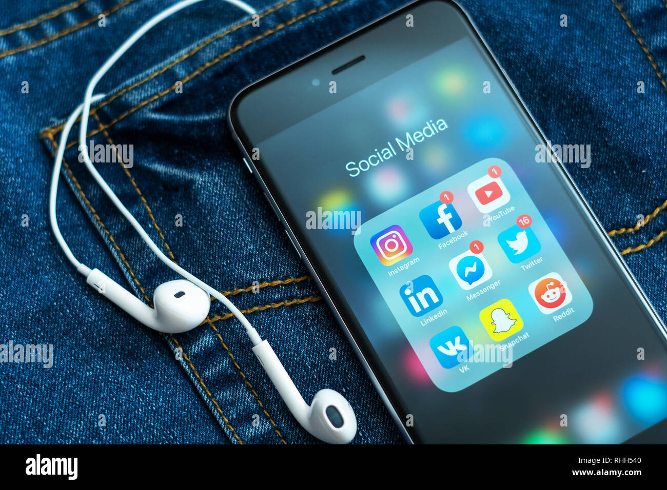 iPhone with icons of social media: instagram, youtube, reddit, facebook, twitter, snapchat on the screen. Social media icons. Denim jeans background - Stock Image