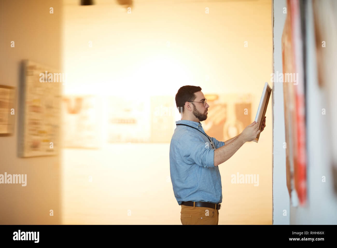 Man Appraising Pictures in Gallery Stock Photo