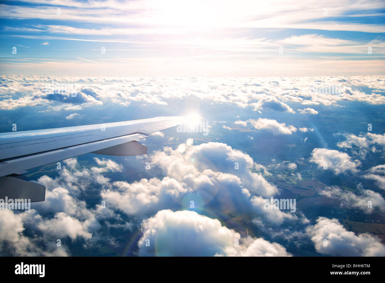 plane wing with beautiful white clouds in background at sunset Stock Photo